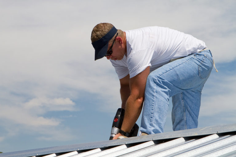 roofing contractor installing metal roofing in Lansing, MI